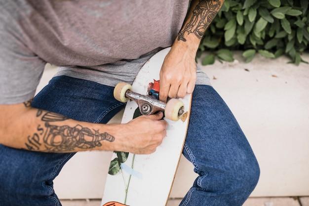 彼の手に入れ墨を入れたスケートボーダースケートボードのホイールを固定する