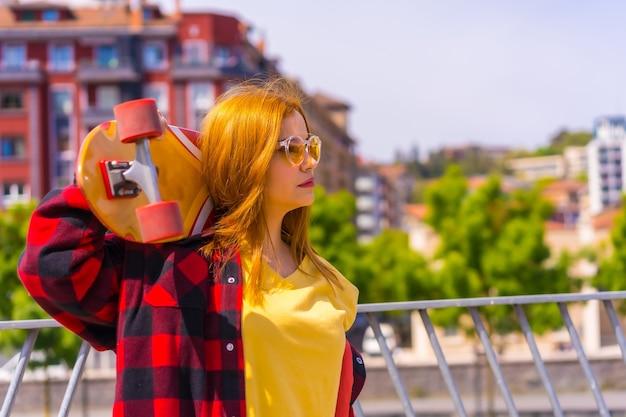 スケートボードを右に向けたポーズで、黄色のシャツ、赤い格子縞のシャツ、サングラスを着たスケートボーダーの女性