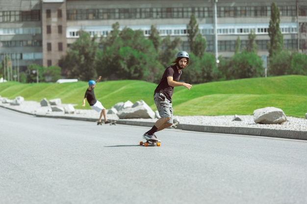 Skateboarders doing a trick at the city's street in sunny day