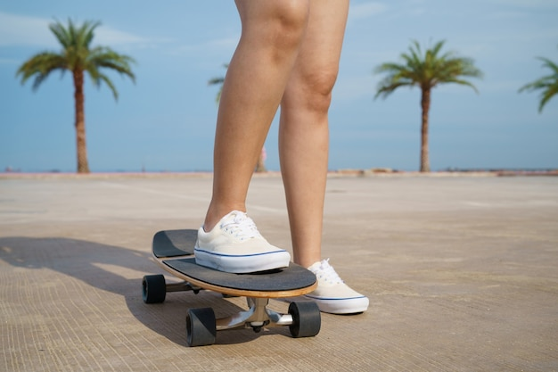 Skater close up of the legs with palm trees background
