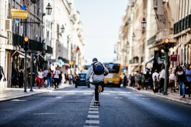 Skater cruises in thew middle of the road downtown crowded lisboa.