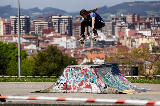 Skater doing a trick in a skatepark with the view of the city