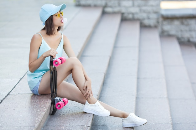 Skater girl. attractive young woman outdoors holding skate. beautiful woman in summer time.