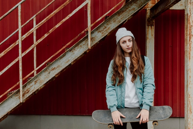 Ragazza pattinatrice che tiene il suo skateboard davanti a lei