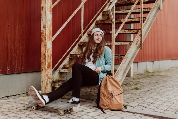 Девушка фигуристка в городе сидит на лестнице длинный вид