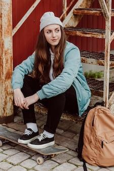 階段に座って都会のスケーターの女の子