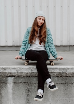 スケートに座っている都会のスケーターの女の子
