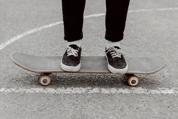 彼女のスケートボードに立っているスケーターの女の子の足