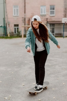 Ragazza pattinatrice in sella al suo skateboard
