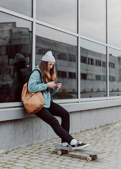 Ragazza pattinatrice nella seduta urbana accanto a un edificio