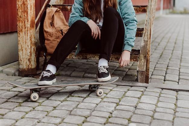 Ragazza del pattinatore nell'urbano che si siede sulla vista frontale delle scale