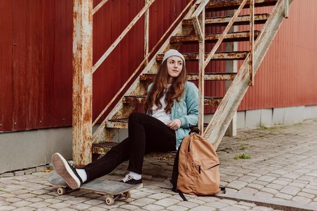 Ragazza del pattinatore nell'urbano che si siede sulla vista lunga delle scale