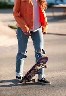 Skater holding board with foot close up