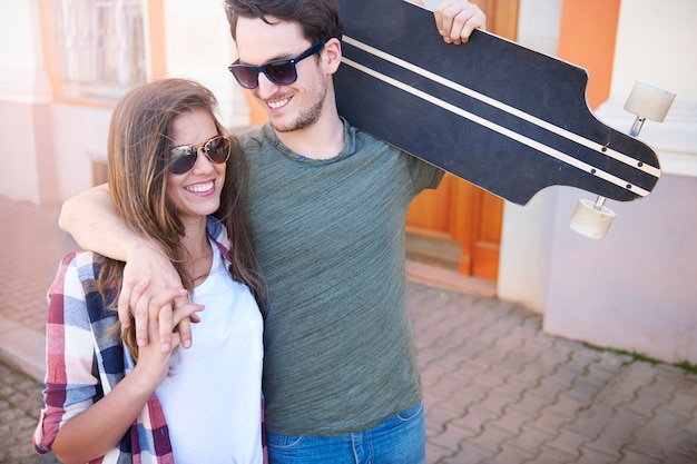 Uomo di pattinatore con la sua ragazza che cammina in città