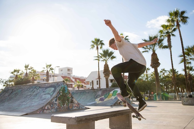 Skater ollies and climbs onto a bench with his skateboard at the skatepark