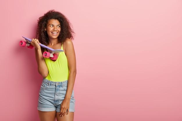 아프로 헤어 스타일, 어두운 피부를 가진 스케이팅 십대 소녀, 롱 보드를 들고 트릭을 수행 할 준비가되었습니다.