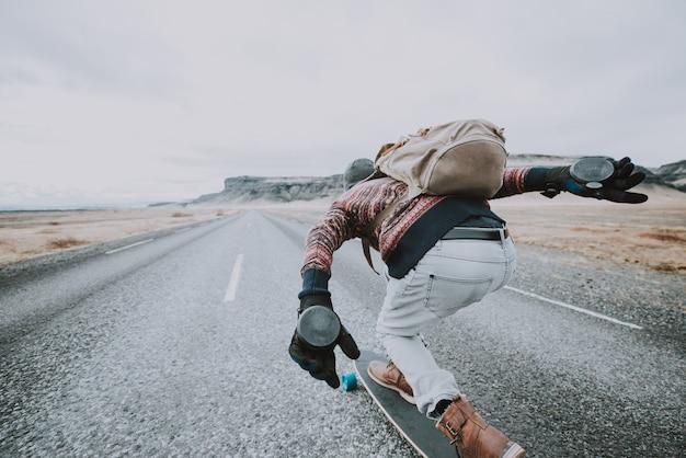 彼のロングボードでアイスランドを旅するスケーター