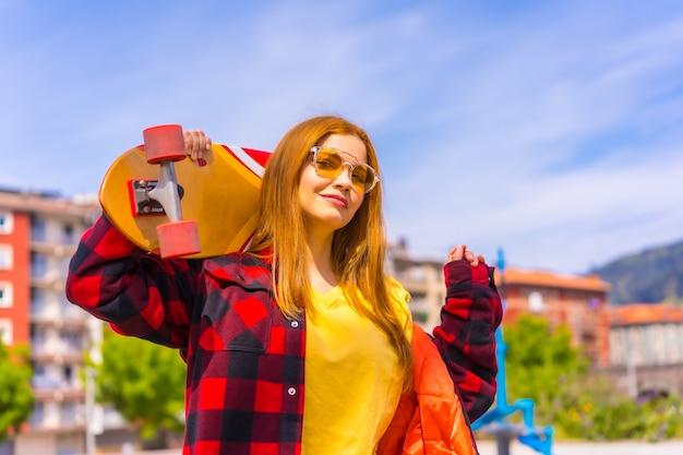 黄色のtシャツ、赤い格子縞のシャツ、サングラスを身に着けたスケーターの女性が、カメラを見ながら肩にボードを置いてポーズをとっている
