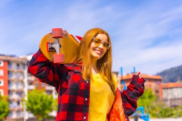 Фигуристка в желтой футболке, красной клетчатой рубашке и солнечных очках позирует с доской на плече, глядя в камеру