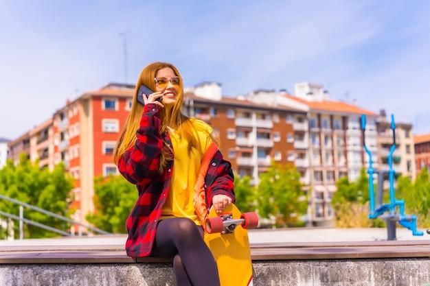 黄色のtシャツ、赤い格子縞のシャツとサングラスを着たスケーターの女性が、街でスケートボードを持って座って、電話で笑顔で電話をかけている