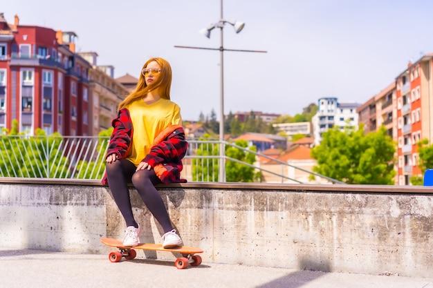 街のベンチにスケートボードで座っている黄色のtシャツ、赤い格子縞のシャツとサングラスのスケーターの女性