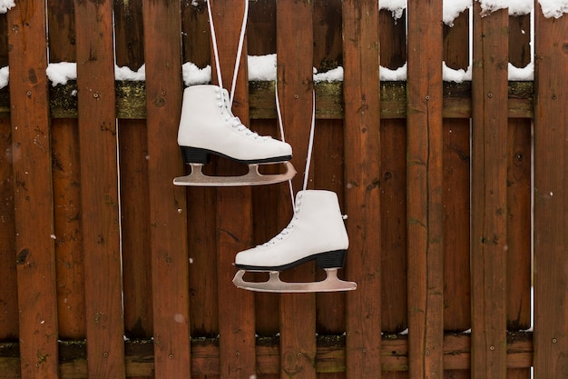 Коньки, висящие на деревянном заборе