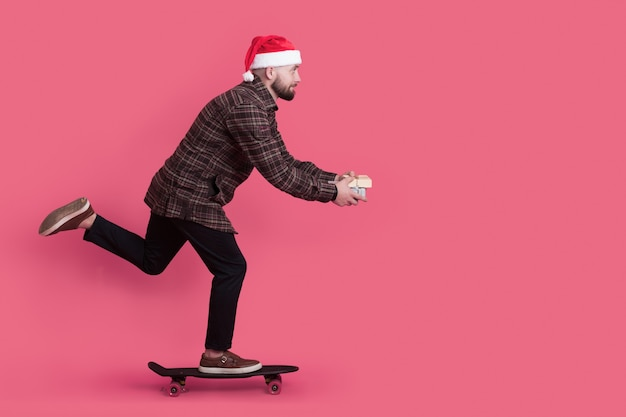 Skating man with a present and red santa hat is advertising something on a studio wall