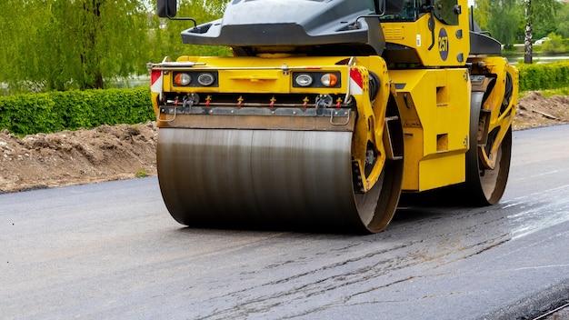 アスファルト圧縮中の道路上のアスファルト用スケートリンク。道路の修理。新しい道を築く