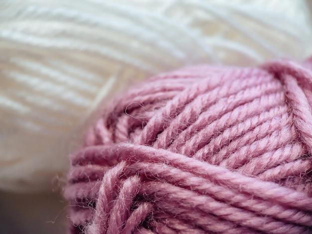 뜨개질을 위한 분홍색과 흰색 아크릴 실 타래. 뜨개질 실의 질감입니다. 바느질에 대 한 배경입니다.
