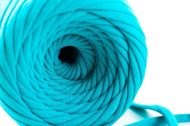 Skein of turquoise knitted yarn isolated on white background
