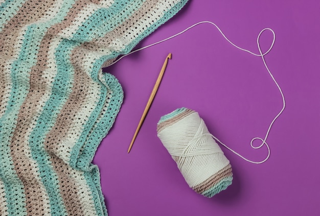 Skein of wool threads with yarn and wooden crochet hook on purple background