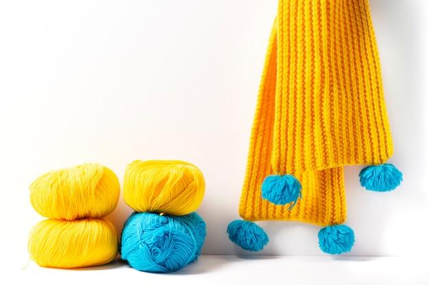 黄色と青の糸のかせ、白い表面にニットのスカーフ
