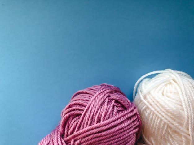 올해의 색상 파란색 클래식 색상의 배경에 뜨개질을 위한 실이 있는 타래. 바느질을 위한 템플릿입니다.