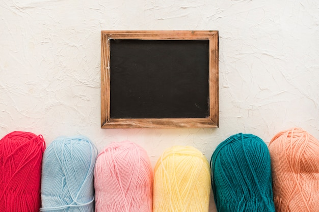 Skeins of yarn near chalkboard