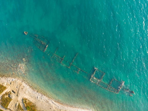 Skeleton of a destroyed seagoing ship near the shore. aerial top view