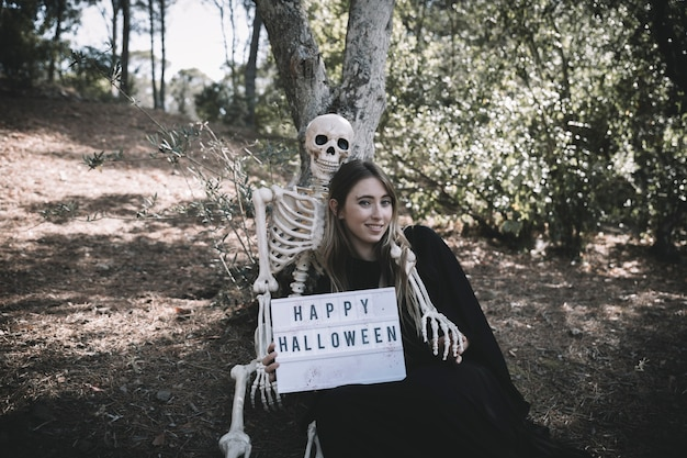 Skeleton embracing smiling lady with tablet in dark suit