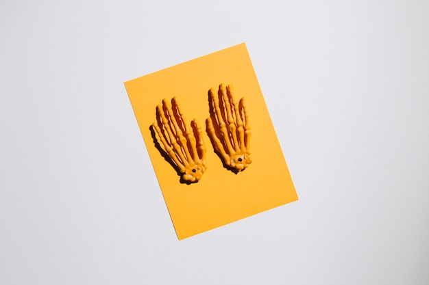 Skeleton hands on piece of paper in middle