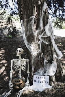 Skeleton holding pumpkin near halloween tablet leaning on tree