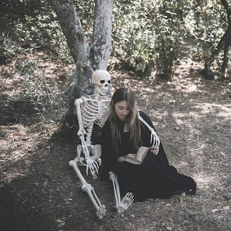 Skeleton hugging lady with book in witch clothes