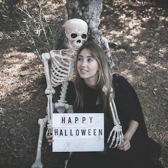 Скелет обнимает леди с таблеткой в темной одежде