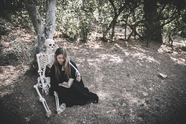 Скелет обнимает читающей леди в одежде ведьм
