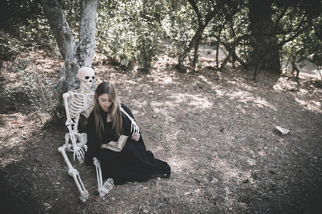 Skeleton hugging reading lady in witch clothes