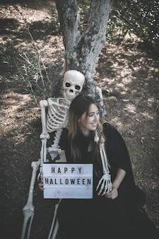 Скелет обнимает улыбается леди с таблеткой в темной одежде