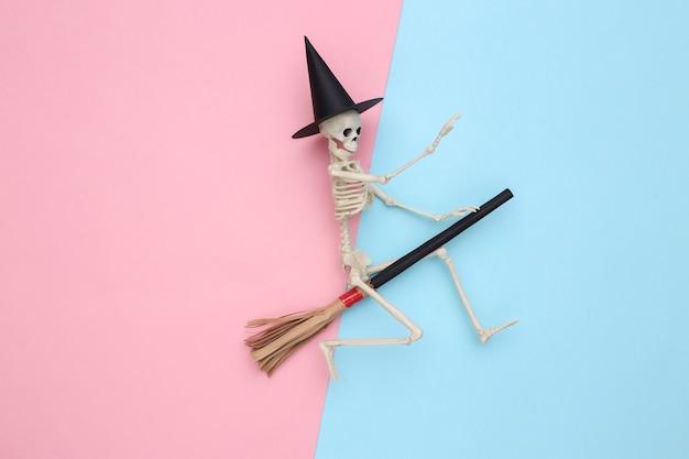 마녀 모자와 빗자루를 쓴 해골. 파란색과 분홍색 파스텔 배경입니다. 할로윈 최소한의 개념입니다. 평면도. 플랫 레이