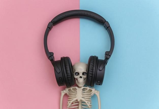 블루 핑크 파스텔 배경에 큰 검은 스테레오 헤드폰의 해골. 평면도