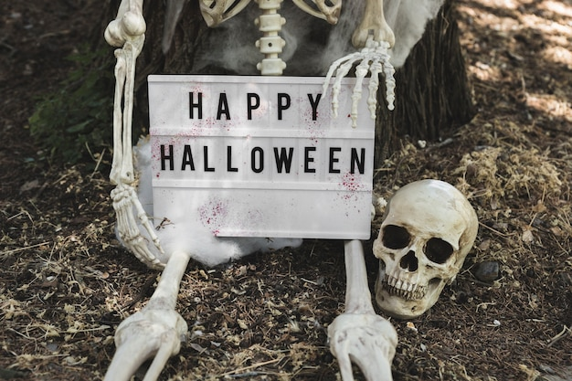 Skeleton leaning on tree and holding halloween tablet