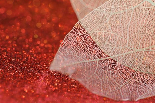 빛나는 bokeh와 붉은 반짝이 배경에 해골 잎