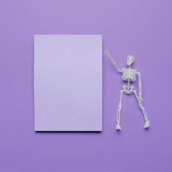 Skeleton pointing a blank space for text with halloween vibes