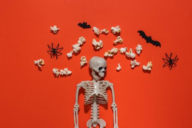オレンジ色の明るい背景にスケルトン、ポップコーン、装飾的なコウモリとクモ。ハロウィーンの構成