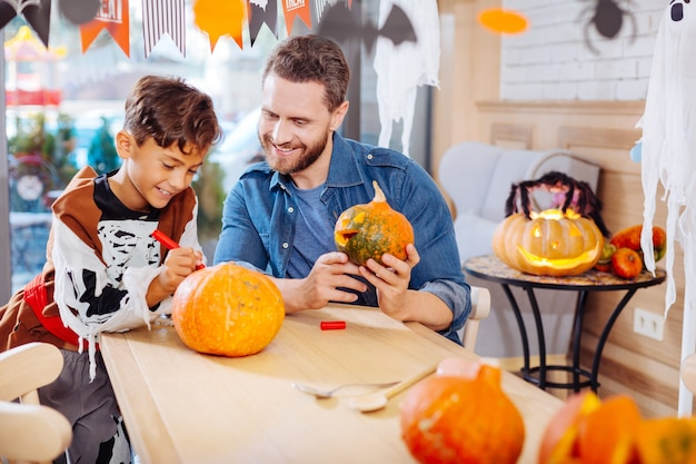 Skeleton and pumpkin. handsome dark-haired boy wearing skeleton suit coloring pumpkin with his bearded loving father